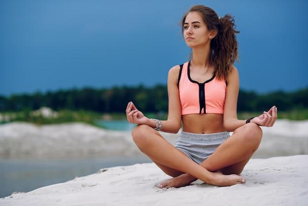 De gezonde vrouw het praktizeren yoga en mediteert op het strand in het zand dichtbij van blauwe cloudly hemel