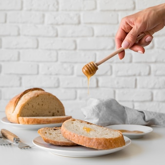 De gietende honing van het vooraanzichthand over broodplak