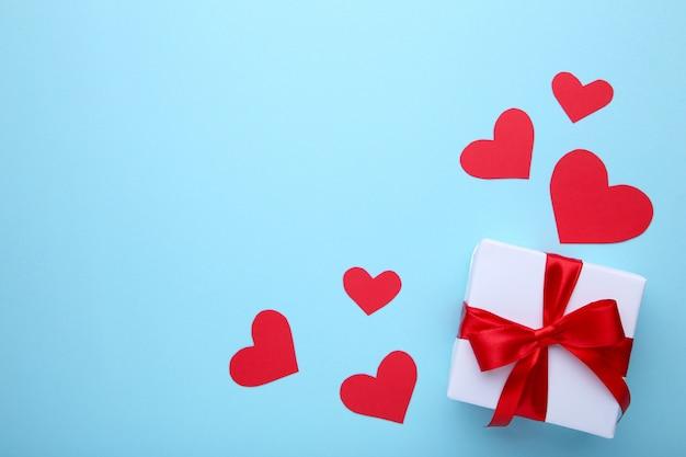 De gift van de valentijnskaartendag met harten op blauwe achtergrond