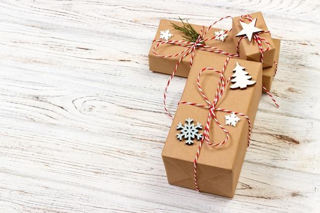 De giftdoos van kerstmis die door sneeuwvlok op houten achtergrond wordt verfraaid