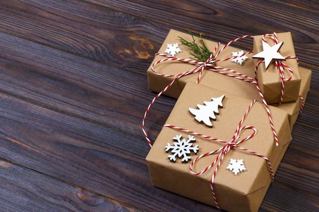 De giftdoos van kerstmis die door sneeuwvlok op houten wordt verfraaid