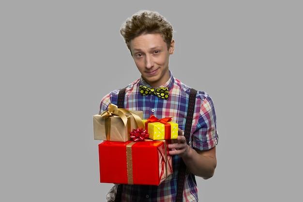 De giftdozen van de tienerjongenholding. portret van tiener met stapel geschenkdozen en camera kijken. vakantie verrassing concept.