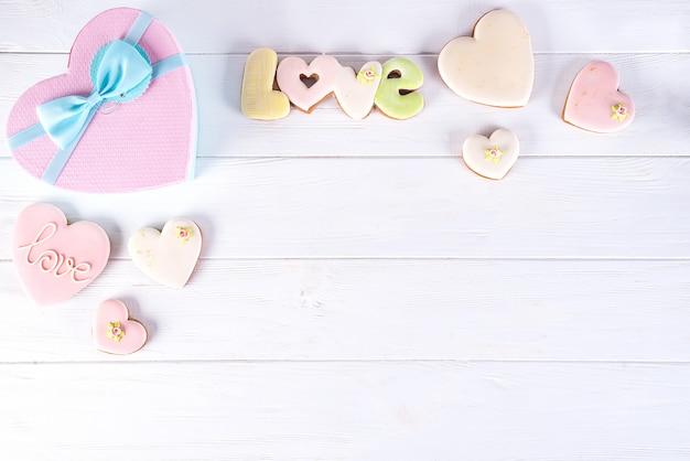 De giftdozen van de valentijnskaartendag met hartkoekjes op witte houten achtergrond.