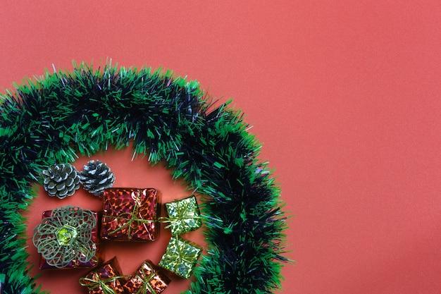 De giftvakjes en decoratie van kerstmis op rode kunstdocument achtergrond.