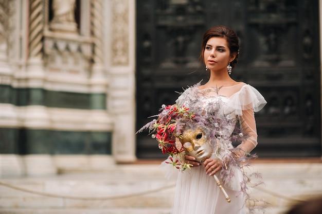 De girlbride is met prachtig bloemenpatroon als masker in florence, stijlvolle bruid in een trouwjurk