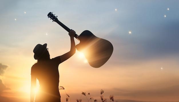 De gitaar van de musicusholding ter beschikking van silhouet op de achtergrond van de zonsondergangaard