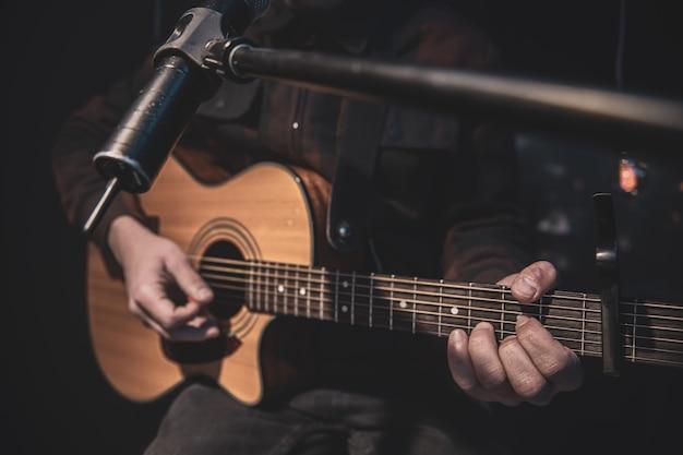 De gitarist speelt een akoestische gitaar met een capo voor een microfoon