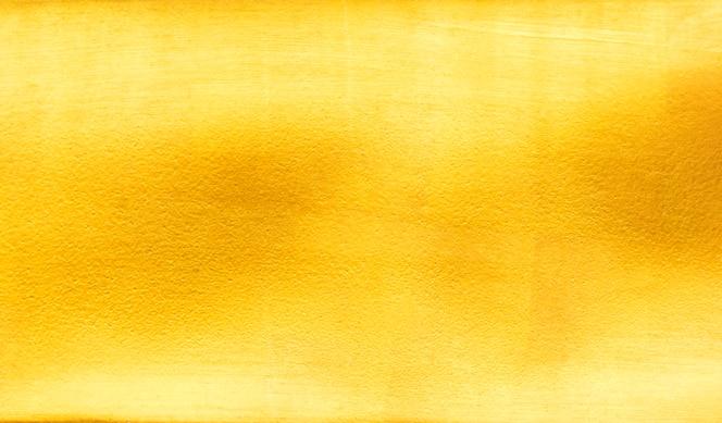 De glanzende gele textuur van de bladgoudfolie