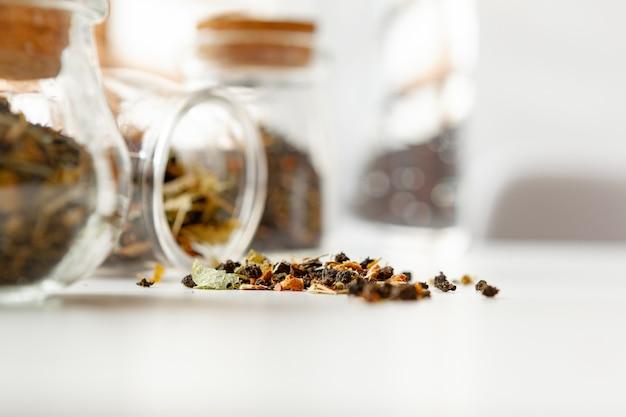 De glaskruiken met droge theebladen sluiten omhoog op witte lijst