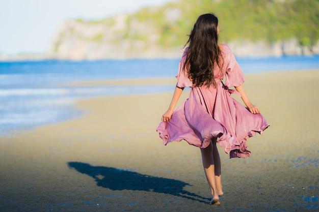 De glimlach gelukkige gang van de portret mooie jonge aziatische vrouw op het tropische openluchtstrand van het aardstrand