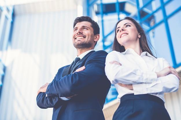 De glimlach man en vrouw staan op de achtergrond van het kantoorcentrum