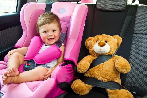De glimlach van het babymeisje in auto
