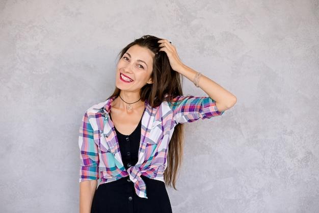 De glimlach van het hipstermeisje die haar tanden tonen en met haar spelen
