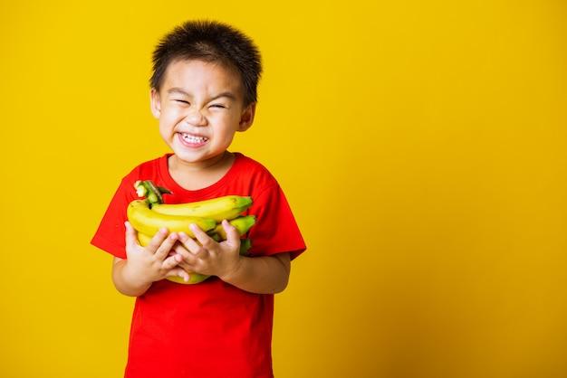 De glimlach van het jonge geitje weinig jongen houdt het fruit van de bananenkam bij de hand