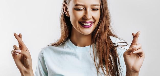 De glimlach van het mooie jonge meisje kruiste haar vingers voor geluk en deed een wens op een witte geïsoleerde grijze achtergrond.
