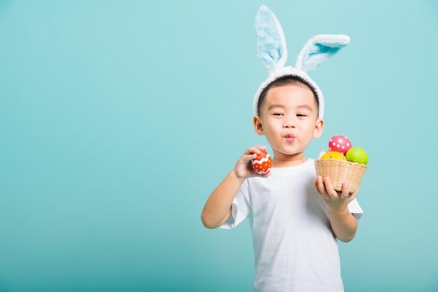 De glimlach van weinig kindjongen die konijntjesoren en wit t-shirt dragen, houdt mand met volledige paaseieren
