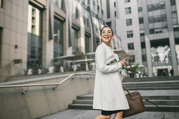 De glimlachende aantrekkelijke aziatische bedrijfsvrouw in glazen met een krant ontmoet een collega dichtbij bureaucentrum
