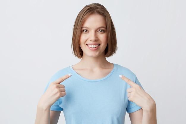 De glimlachende aantrekkelijke jonge vrouw in blauw t-shirt voelt zich zelfverzekerd en wijst met vingers op beide handen naar zichzelf
