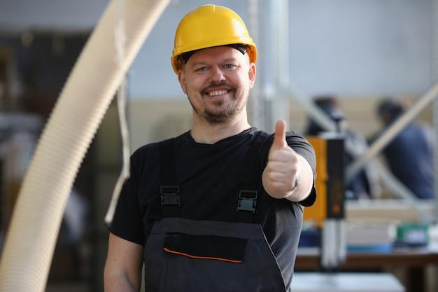 De glimlachende arbeider in gele helm toont teken met duim omhoog bij wapenportret bevestigt. handmatige baan diy inspiratie schrijnwerkerij opstarten idee fix winkel bouwvakker industriële opleiding beroep carrière carrière concept