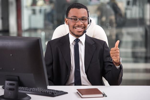 De glimlachende assistent gebruikt een hoofdtelefoon in een callcenter.