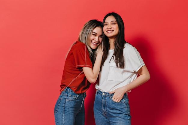 De glimlachende aziatisch ogende vrouwen stellen op rode muur