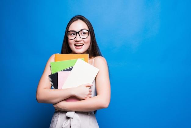 De glimlachende aziatische boeken en het dossier van de studenteholding, hogeschool of schoolstudent en onderwijsconcept dat op blauwe muur met exemplaarruimte wordt geïsoleerd.