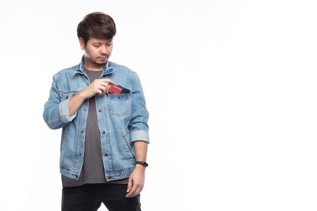 De glimlachende aziatische mens die een creditcard houdt, zet in de zak van de spijkerbroek