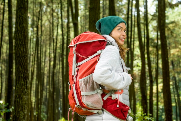 De glimlachende aziatische reizigersvrouw met rugzak onderzoekt