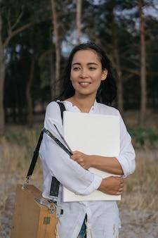 De glimlachende aziatische verfborstel van de kunstenaarsholding, canvas en schildersdoos. portret van koreaanse vrouwenschilder die inspiratie zoekt