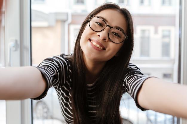 De glimlachende aziatische vrouw breidt handen bij camera uit