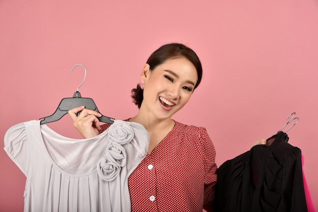 De glimlachende aziatische vrouw geniet van het winkelen kleren.