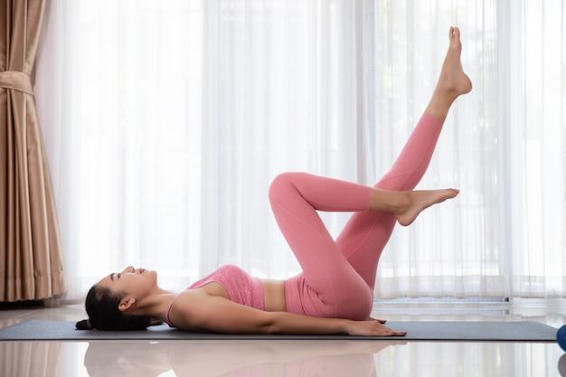 De glimlachende aziatische vrouw oefent thuis, buik oefeningen yoga.