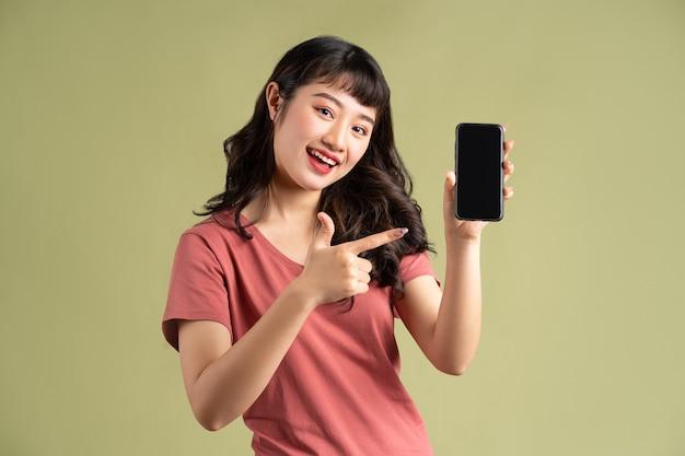 De glimlachende aziatische vrouw wijst met een leeg scherm haar vinger naar de telefoon