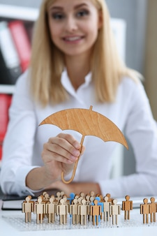 De glimlachende bedrijfsvrouw houdt in hand een miniatuurparaplu