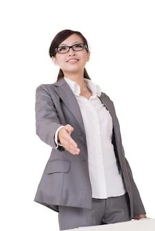 De glimlachende bedrijfsvrouw van aziatische schudt hand met u tegen witte achtergrond.