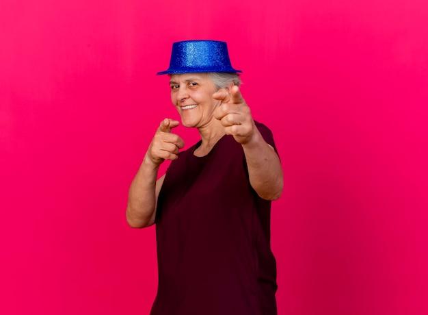 De glimlachende bejaarde die partijhoed draagt kijkt en wijst naar camera met twee handen op roze