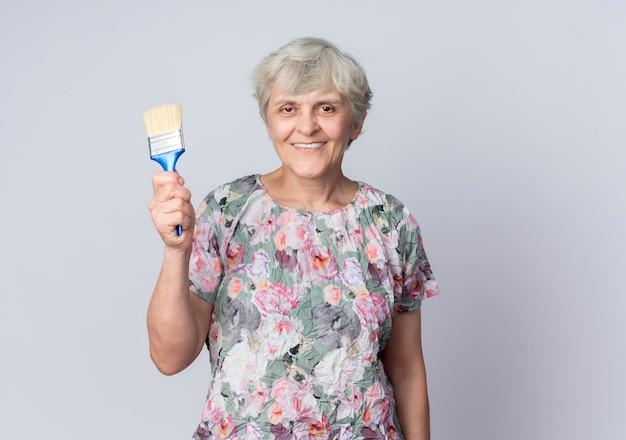De glimlachende bejaarde houdt verfborstel op witte muur wordt geïsoleerd die