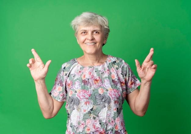 De glimlachende bejaarde kruist vingers die op groene muur worden geïsoleerd