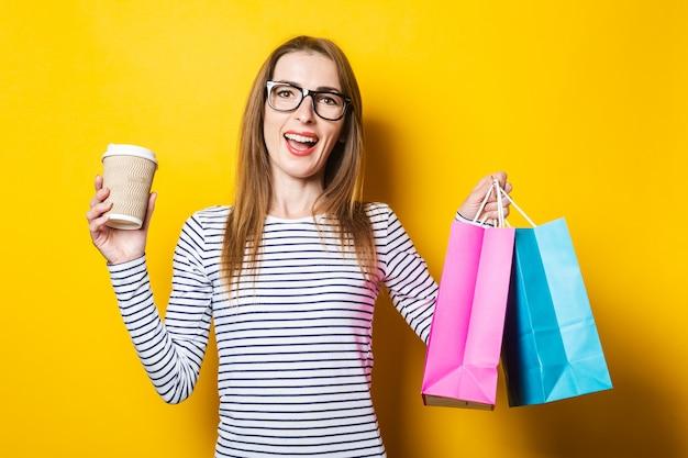 De glimlachende blije jonge vrouw verheugt zich met een papieren beker met koffie en tassen op een gele achtergrond