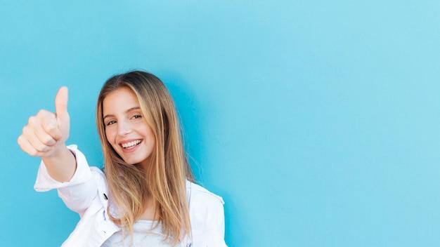 De glimlachende blonde jonge vrouw die duim toont ondertekent omhoog tegen blauwe achtergrond