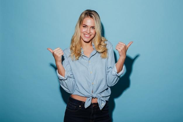 De glimlachende blondevrouw in overhemd het tonen beduimelt omhoog