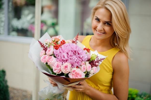 De glimlachende blondevrouw kleedde zich in een gele kleding houdend een roze boeket van bloemen