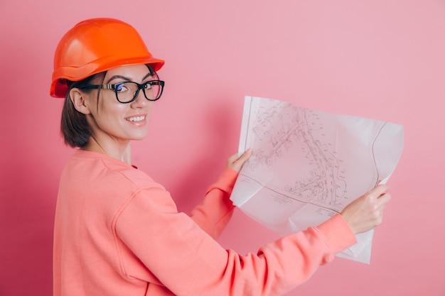 De glimlachende bouwer van de vrouwenarbeider tegen roze achtergrond. helm bouwen.