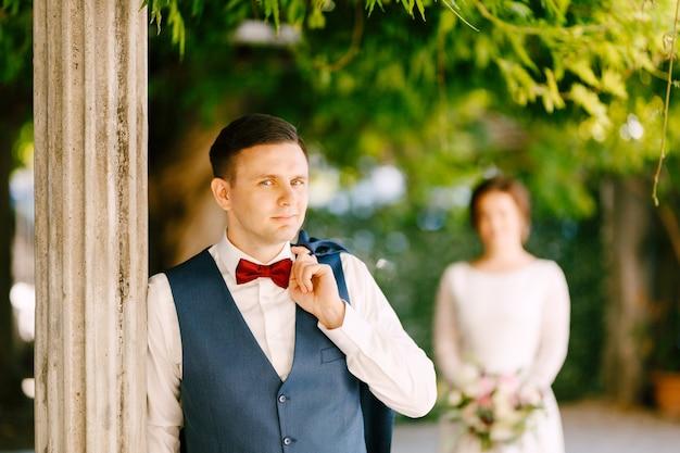 De glimlachende bruidegom gooide zijn jas over zijn schouder. de bruidegom leunde tegen een kolom in de tuin