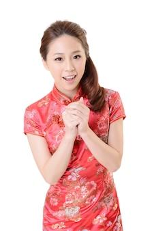 De glimlachende chinese traditionele cheongsam van de vrouwenkleding bij nieuwjaar