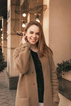 De glimlachende dame draagt een bruine jas, poseert op de camera bij de bruine muur van het restaurant, kijkt naar de camera en glimlacht eerlijk