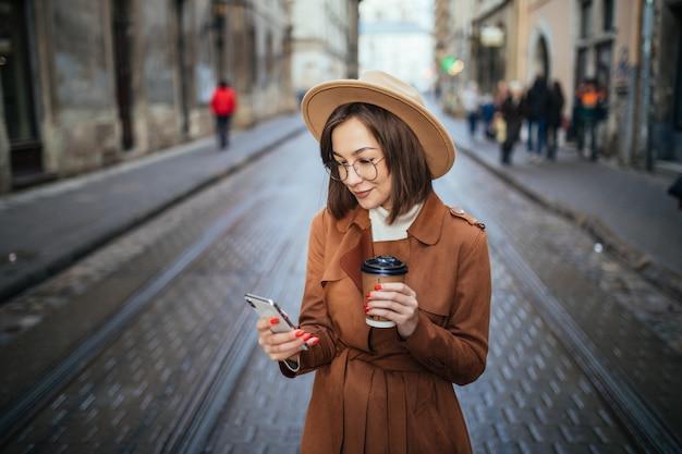 De glimlachende dame heeft een videocall en drinkt koffie terwijl ze buiten in de stad loopt