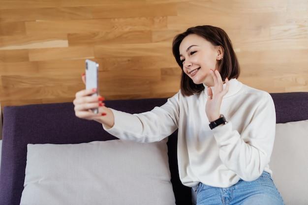 De glimlachende dame in witte sweater heeft een videocall met haar vriend