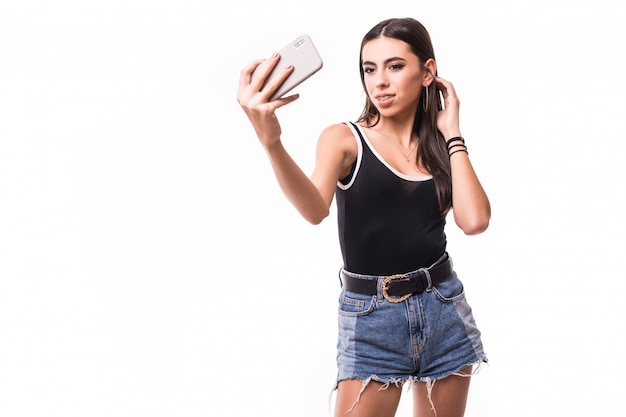 De glimlachende dame maakt in het kort selfie op haar geïsoleerde telefoon