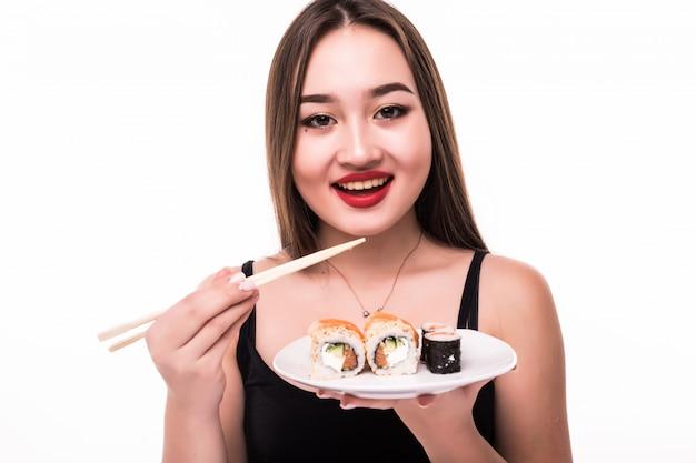 De glimlachende dame met zwart haar en rode lippen proeft suushi-broodjes die houten eetstokjes in haar hand houden
